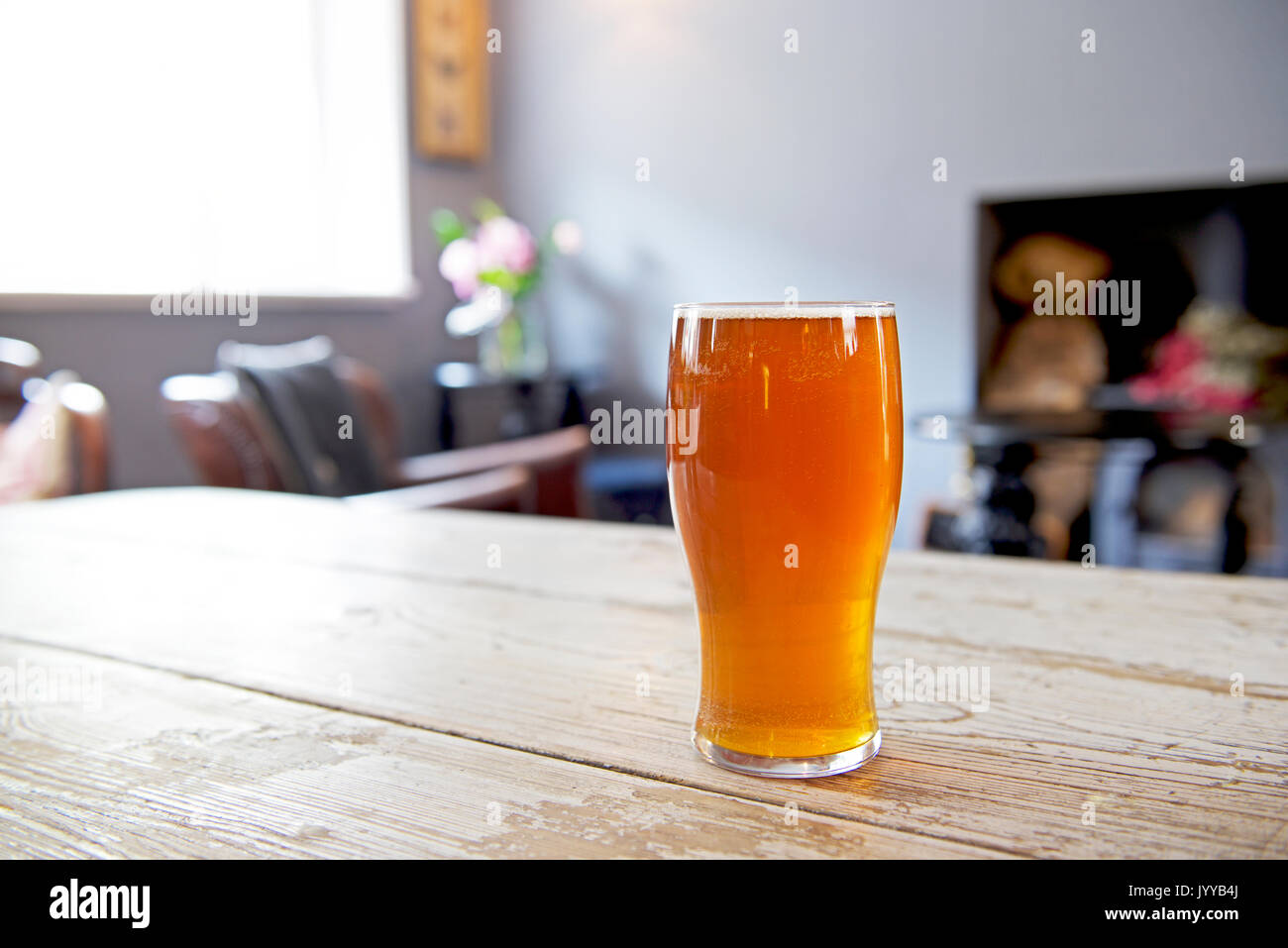 Pint of beer on table in the bar of the Lynn Arms, in the village of Syderstone, North Yorkshire, England UK - Stock Image
