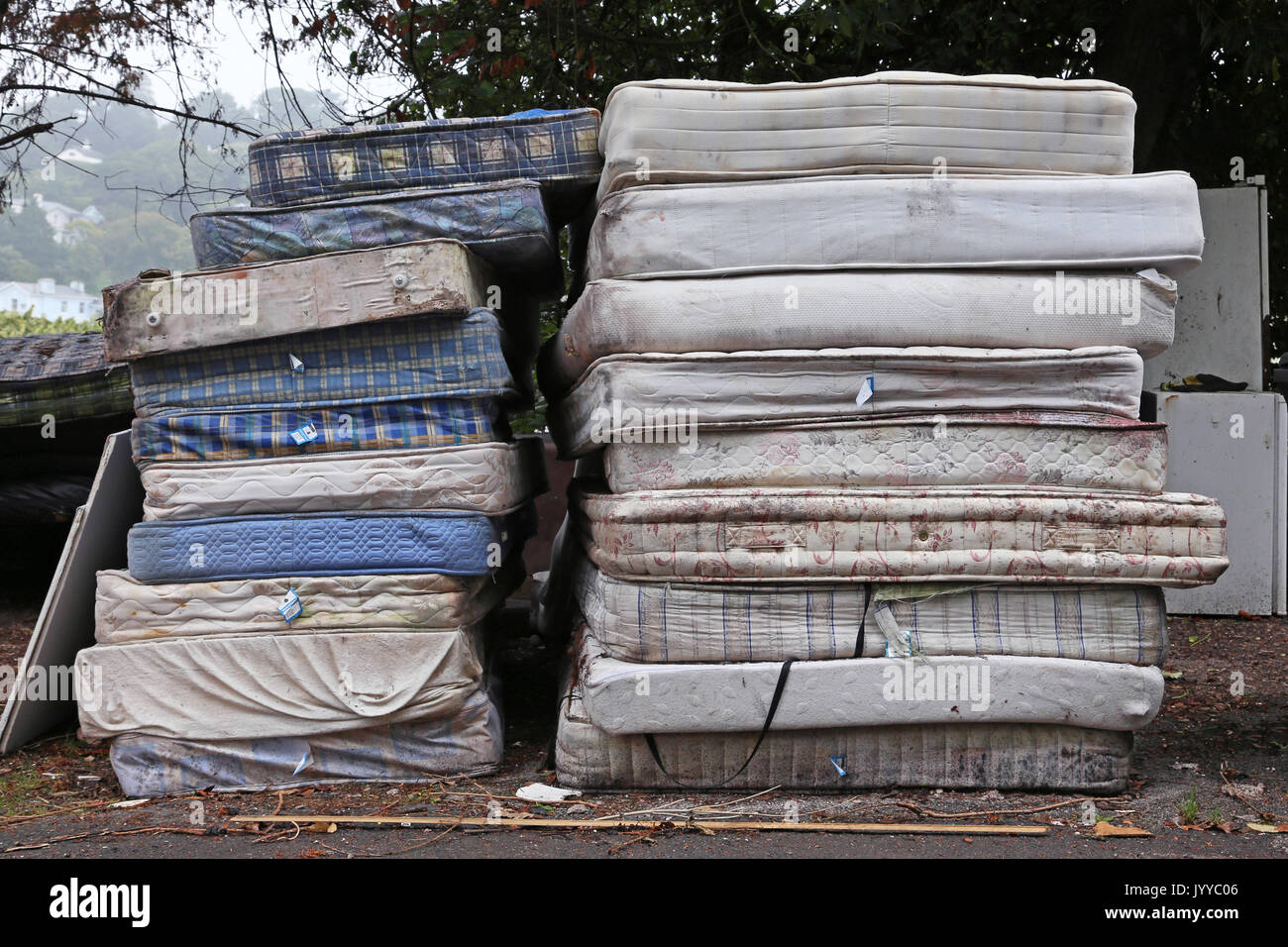 A stack of dirty mattresses are piled up on a roadside in Devon, UK - Stock Image
