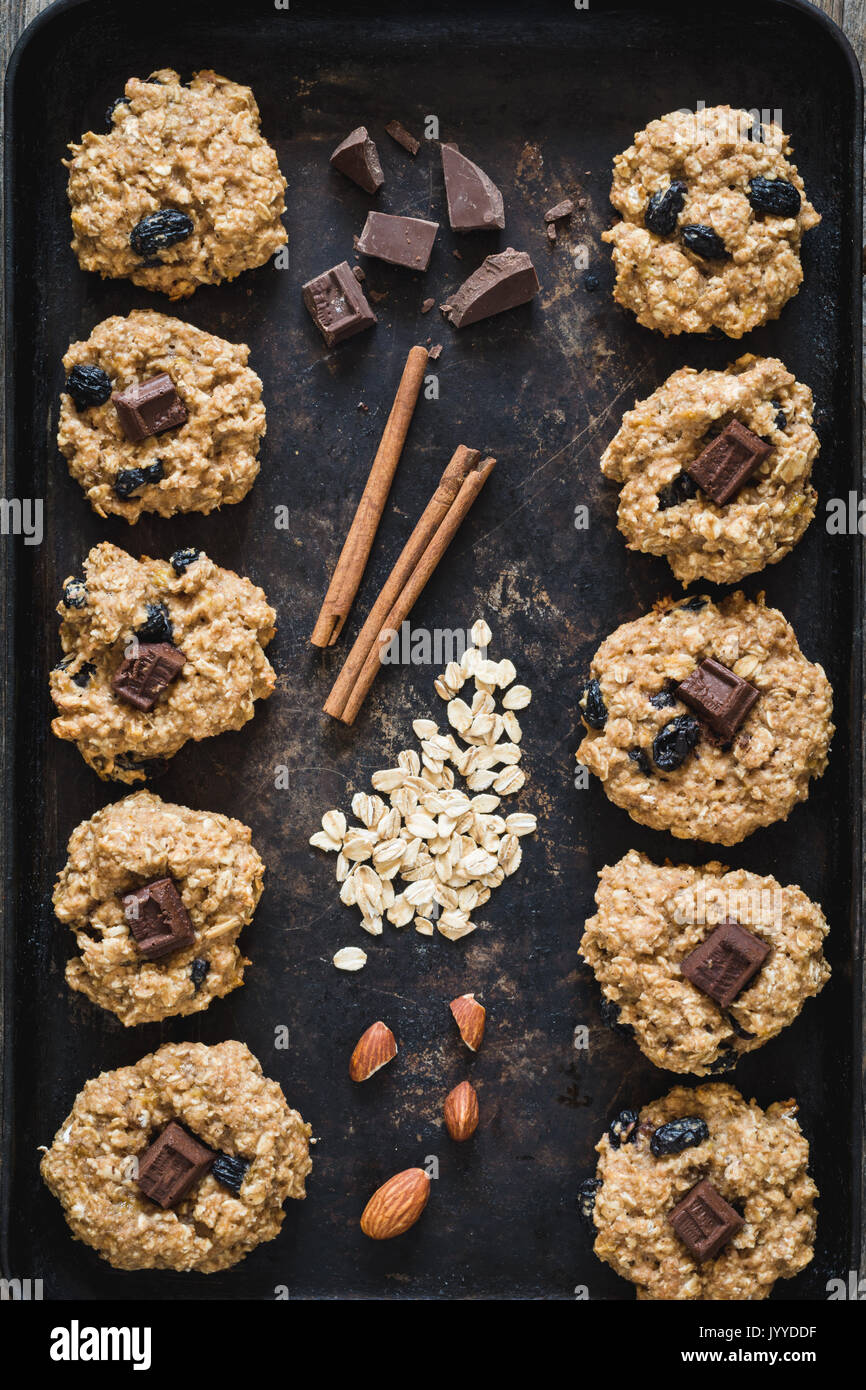 Top view of freshly baked oatmeal raisin cookies with dark chocolate, cinnamon and nuts on old rusty cookies sheet. Stock Photo