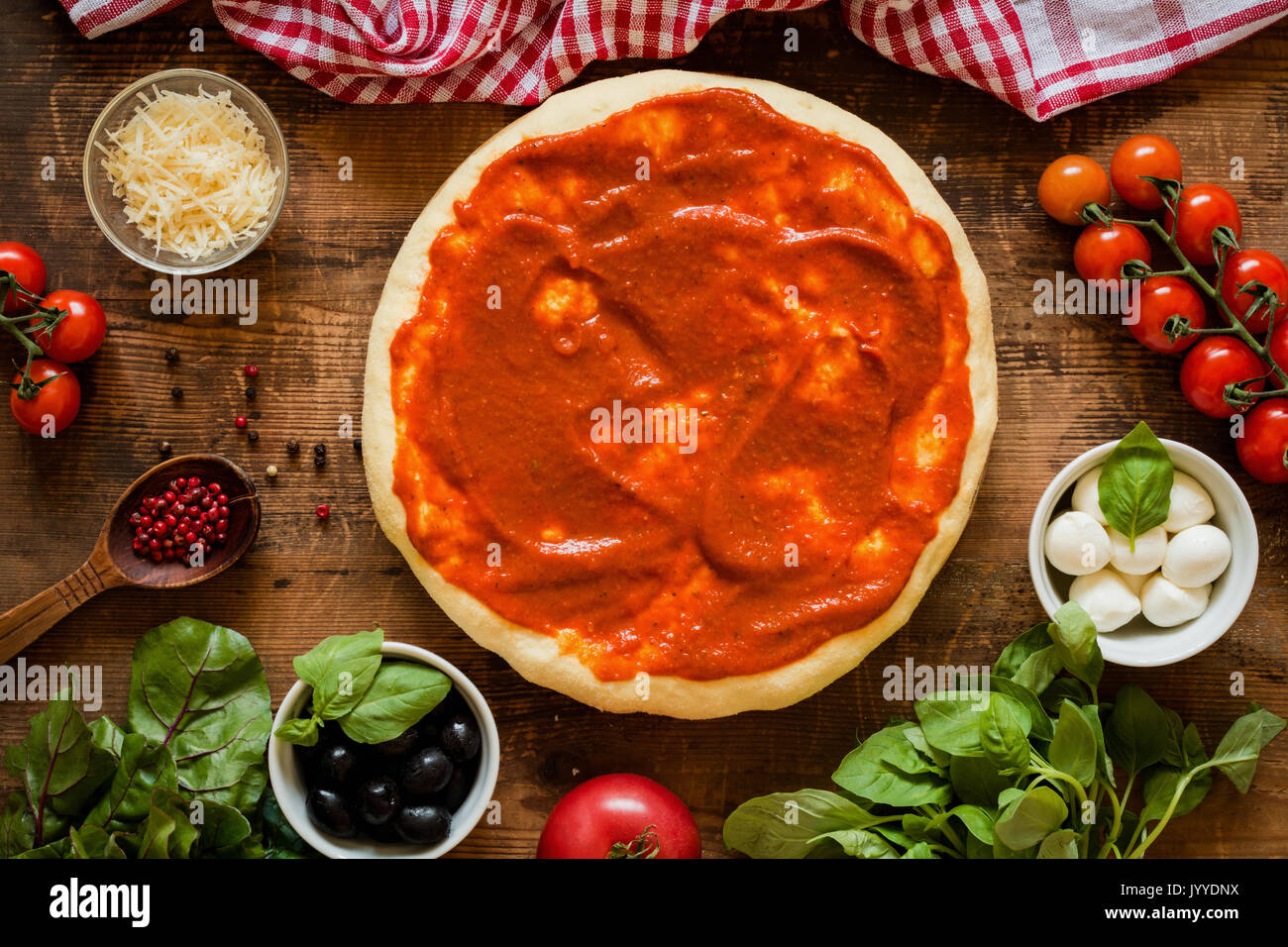 Prepared pizza dough with tomato sauce and ingredients on rustic wooden background. Cherry tomatoes, basil, mozzarella Stock Photo