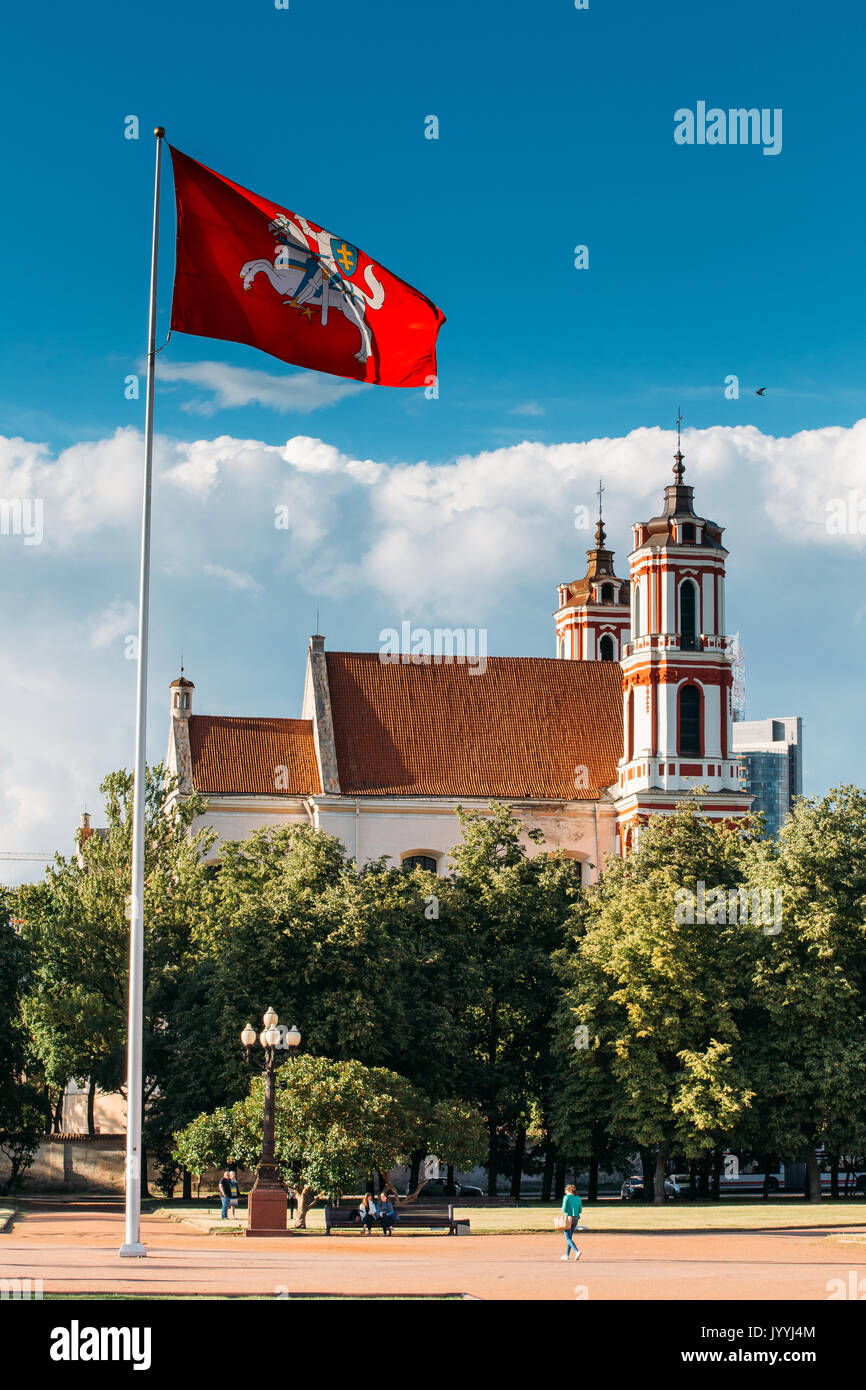 Vilnius, Lithuania. Church Of St Philip And St Jacob, Ancient Roman Catholic Church With Monastery And Red Tile Roof And Flagpole With Historical Flag - Stock Image