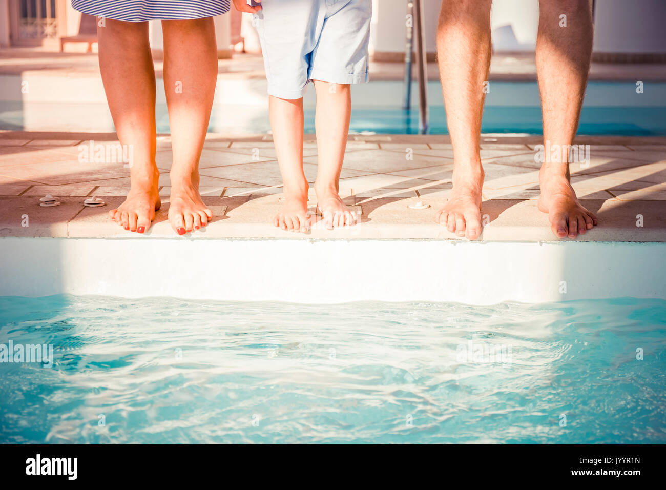 feet of a young family near the pool - Stock Image