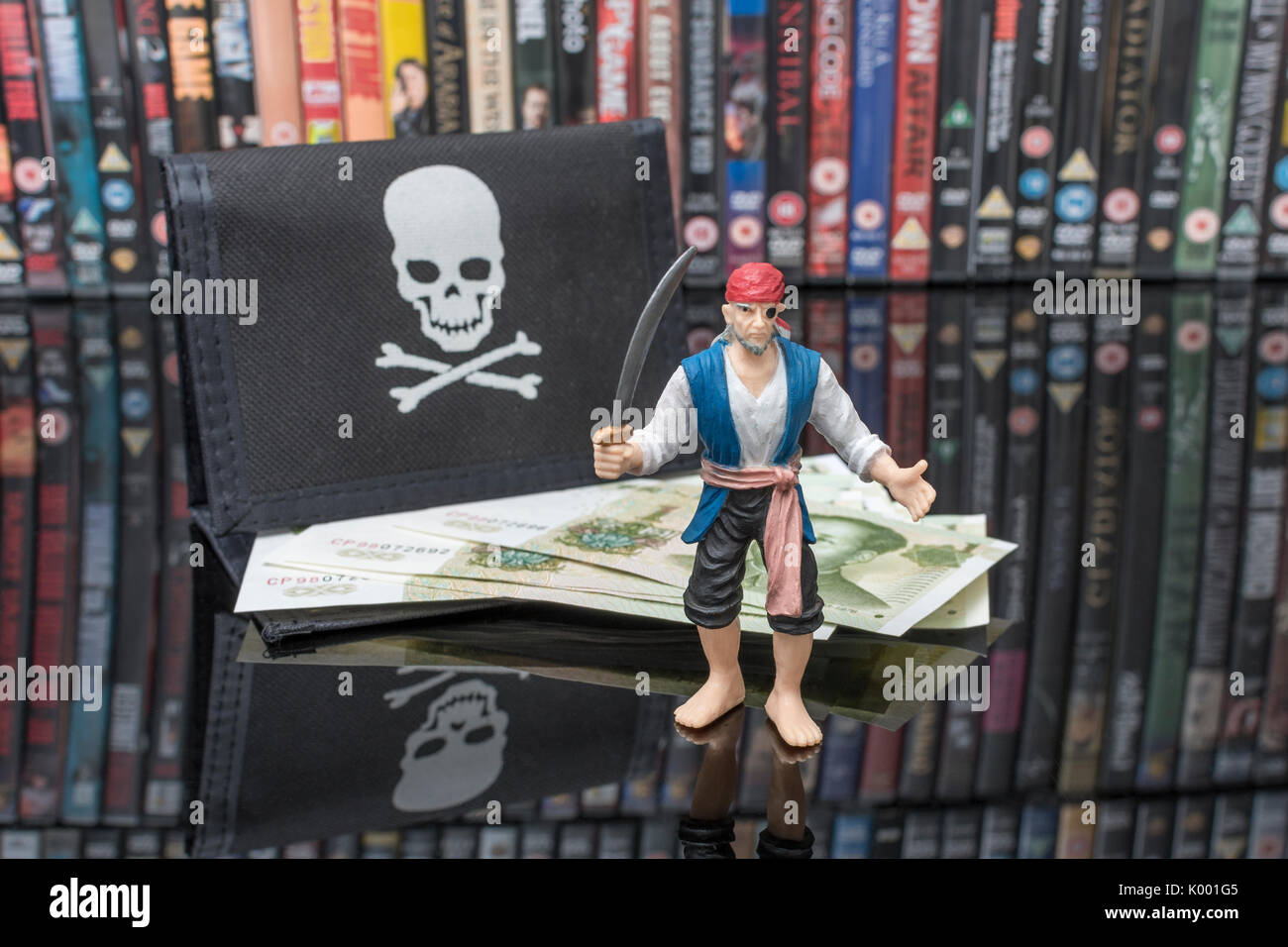 Sword wielding toy pirate standing beside stacks of DVDs (Digital Versatile Disc) - metaphor software piracy, Chinese counterfeit goods & IP theft. - Stock Image