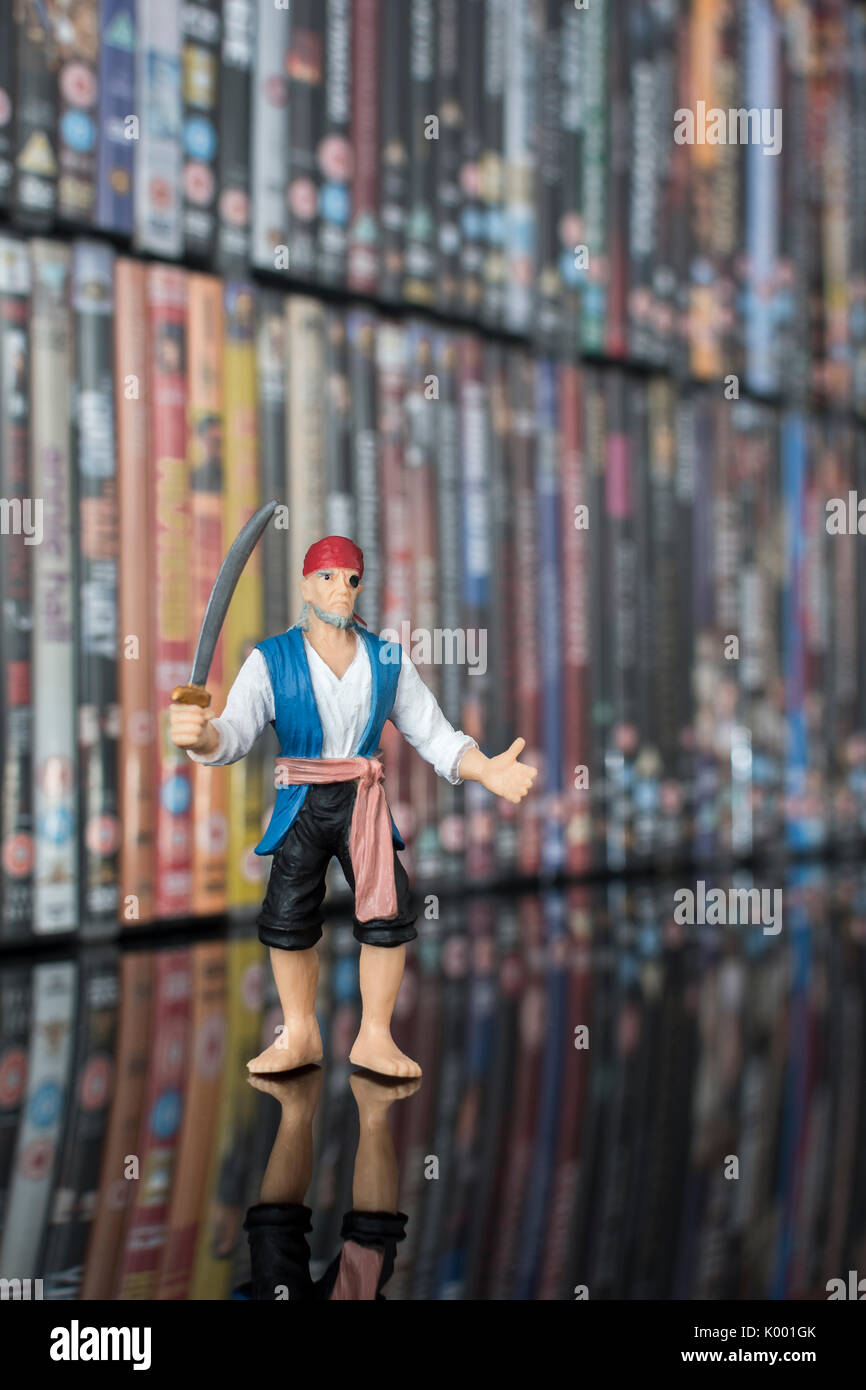 Sword wielding toy pirate standing in front of stacks of DVDs (Digital Versatile Disc) - metaphor software piracy, Chinese counterfeit goods, IP theft - Stock Image