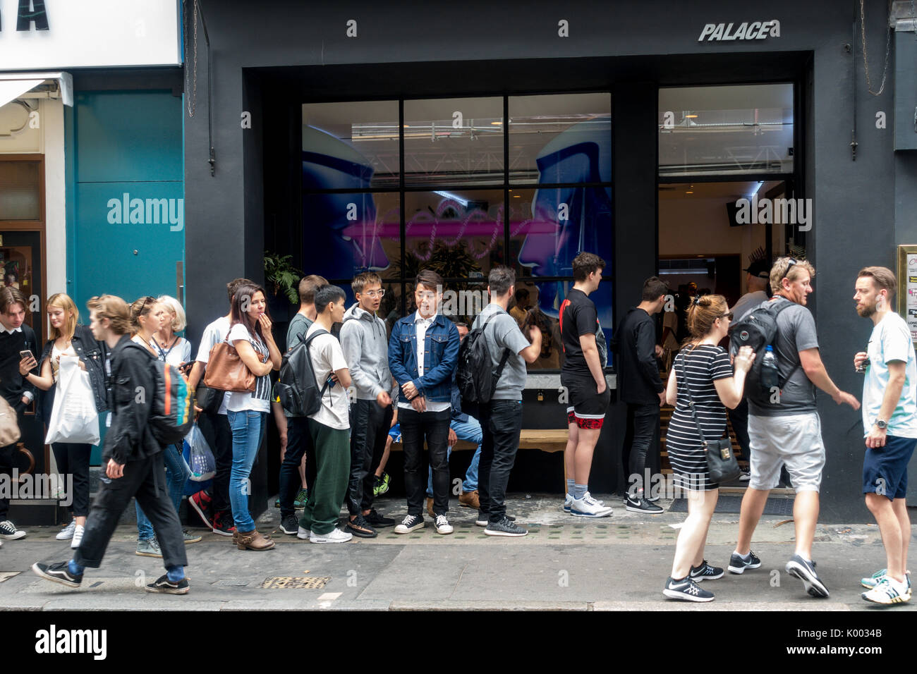 a0eca981 Exterior of Palace skateboard shop, 26 Brewer St, Soho, London W1F 0SW, UK  with long queue of people outside on the pavement sidewalk