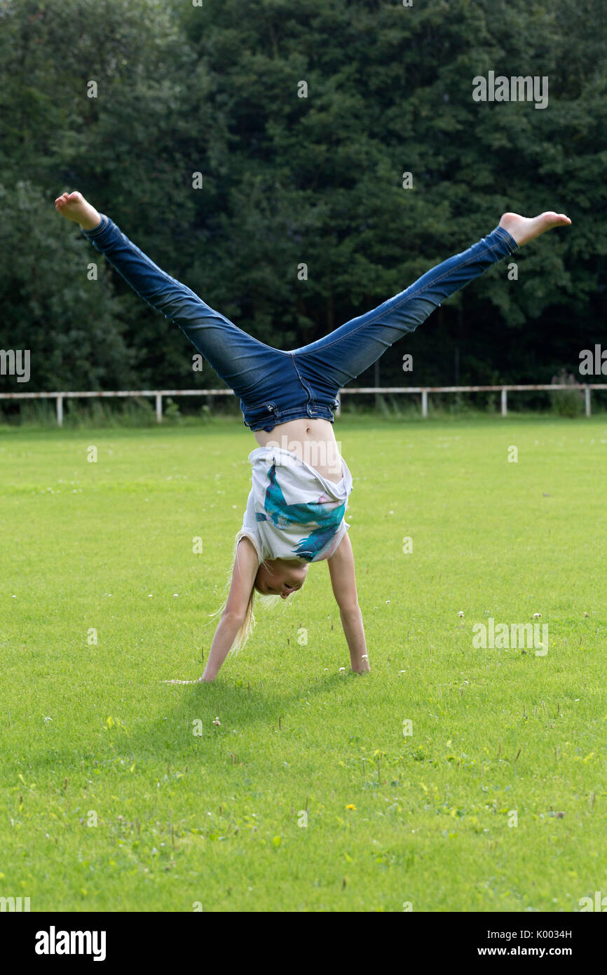 young girl doing a cartwheel - Stock Image