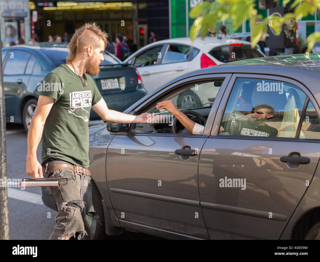 A man receives money from a driver as he finishes cleaning car windshield trying to earn some money for food & shelter. Poverty in Montreal, Quebec - Stock Image