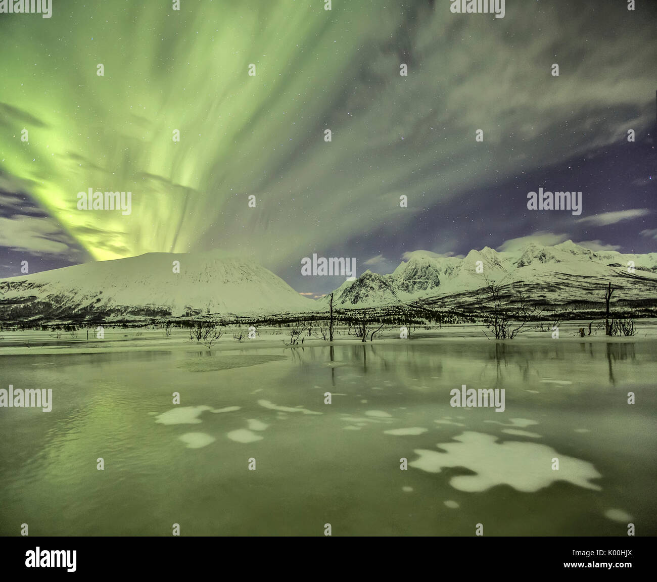 Aurora Borealis on the frozen lagoon of Jaegervatnet Stortind Lyngen Alps Tromsø Lapland Norway Europe - Stock Image