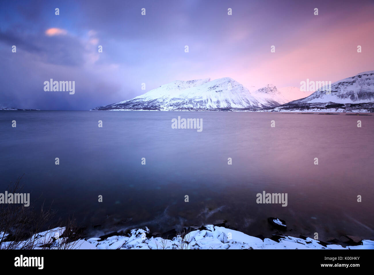 The sky turns pink at sunset and is reflected in the frozen sea Storfjorden Lapland Lyngen Alps Tromsø Norway Europe Stock Photo