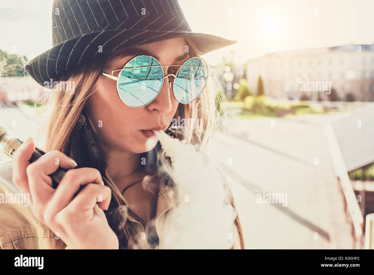Pretty young hipster woman in black hat vape ecig, vaping device at the sunset. Toned image. - Stock Image