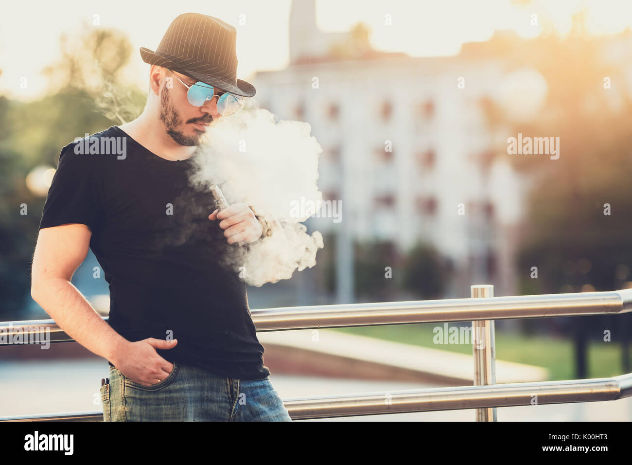 19fc22b89a0 Modern happy young man in hat with a beard fun Vaporizers