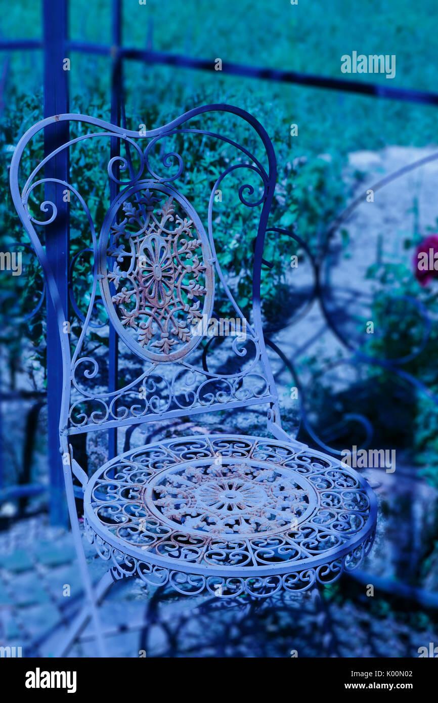 Alter rostiger, romantischer, Stuhl aus Metall, mit verspielten Ornamenten - Stock Image