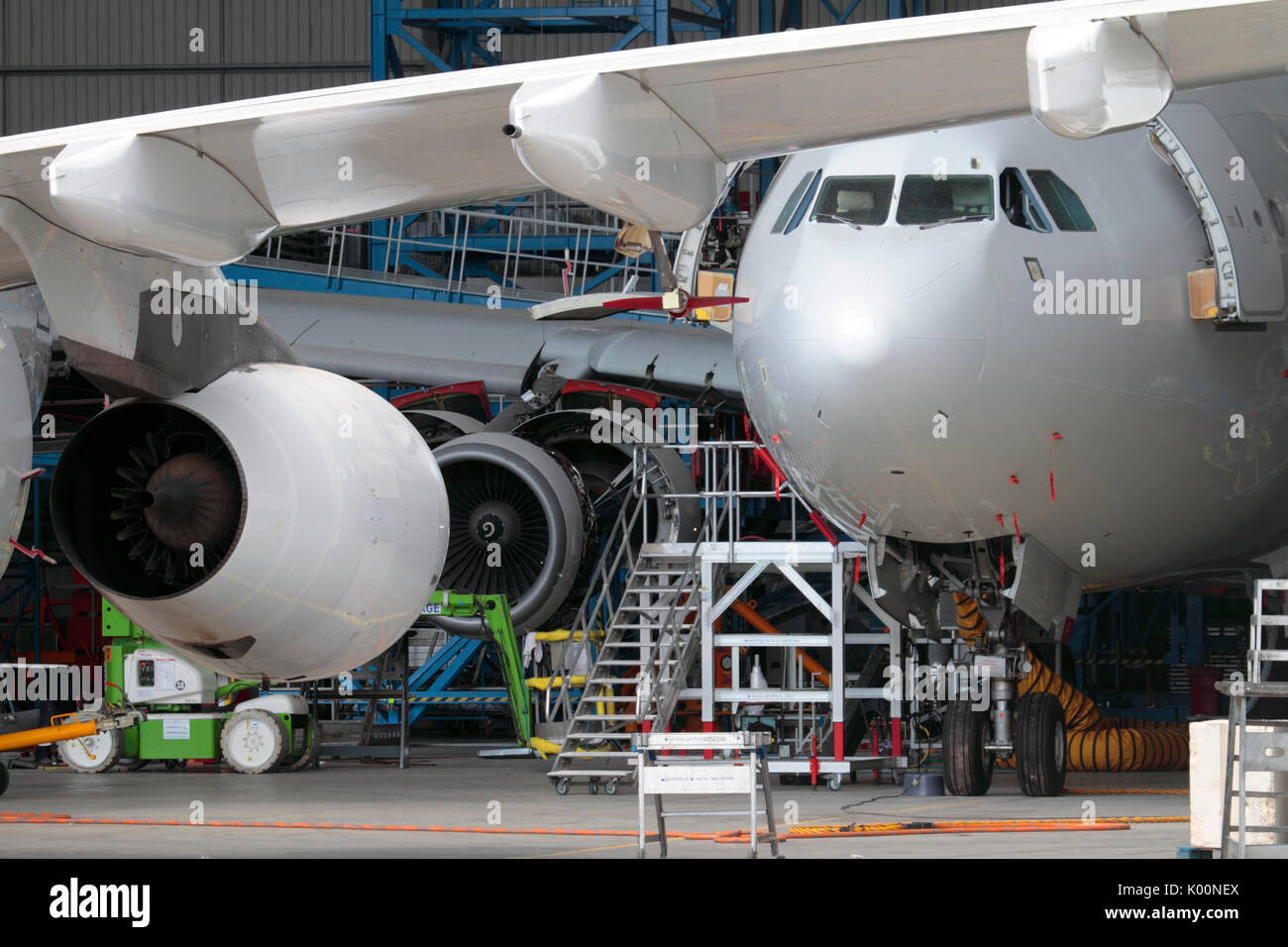 Passenger jet planes undergoing maintenance in a busy aircraft hangar. Aviation engineering as a contributor to economic development and growth of GDP - Stock Image