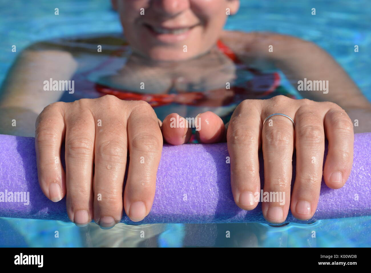Woman in swimming pool, hands on a pool noodle - Stock Image