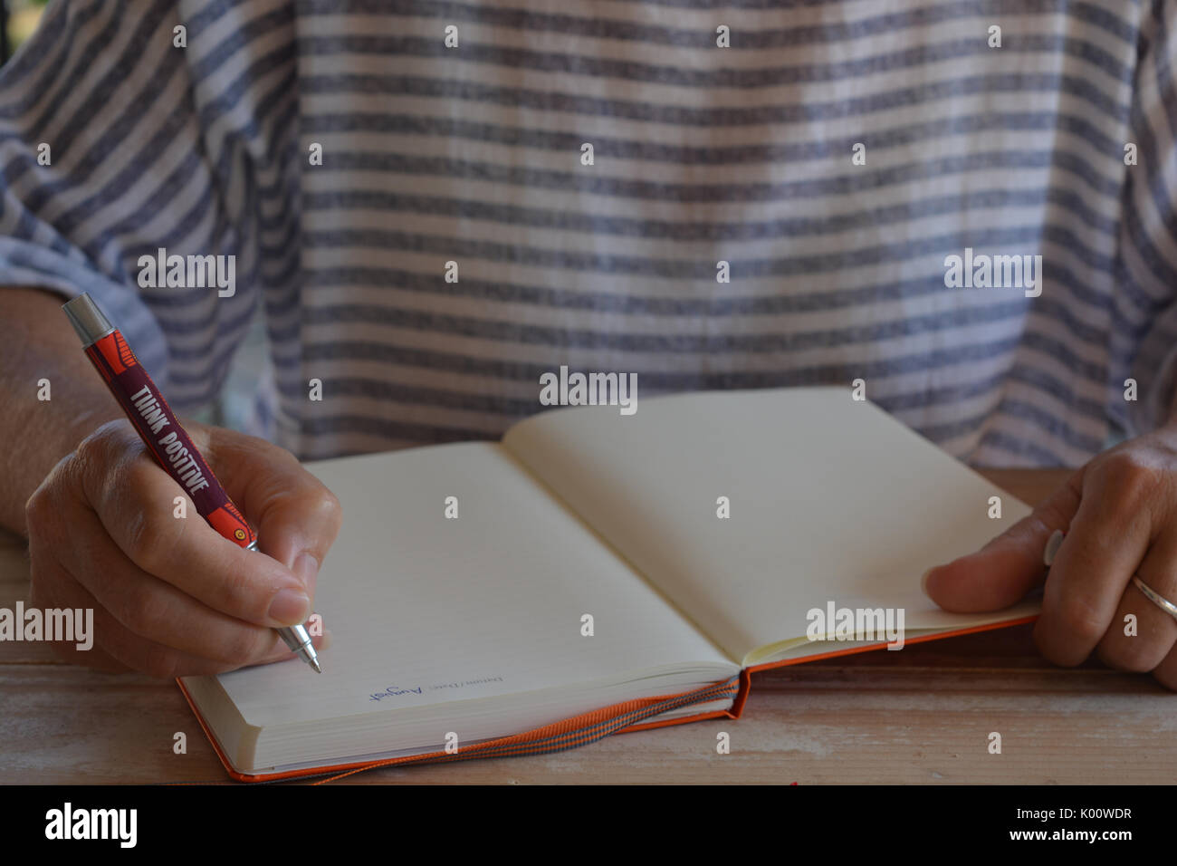 Woman writing up a bullet journal - Stock Image