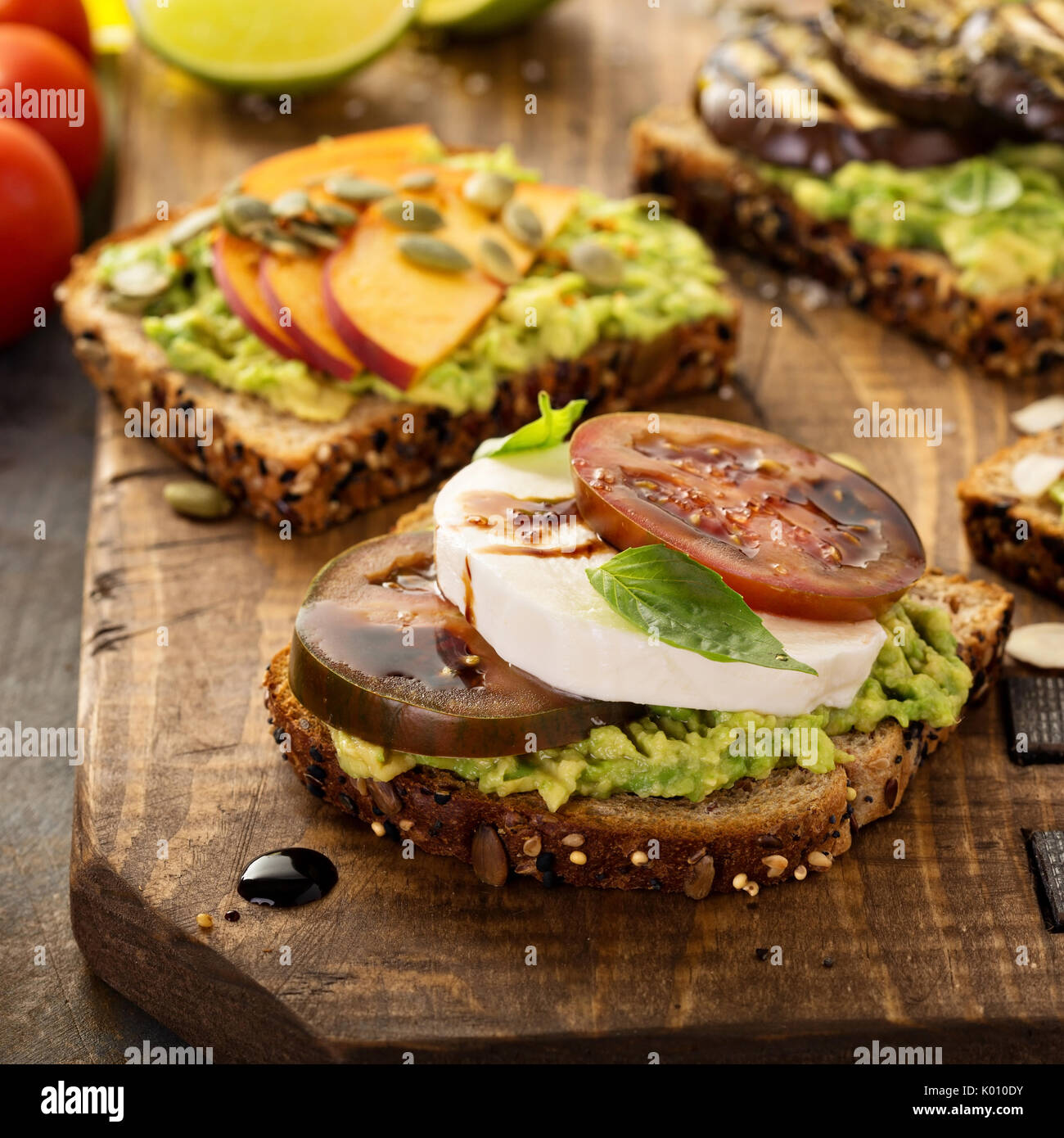 Variety of avocado toasts on a cutting board - Stock Image