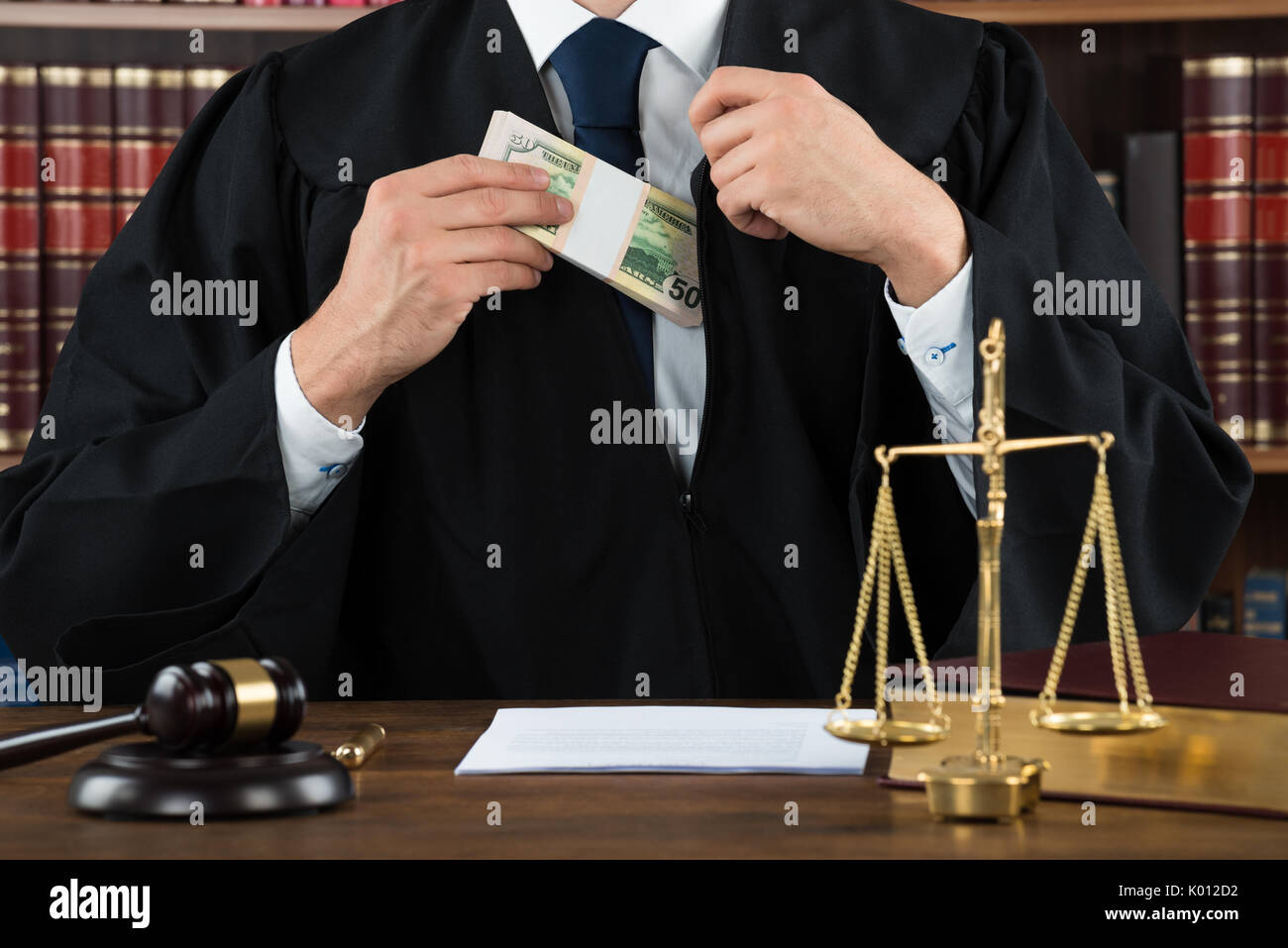 Midsection of corrupt judge putting dollar bundle in pocket at courtroom Stock Photo