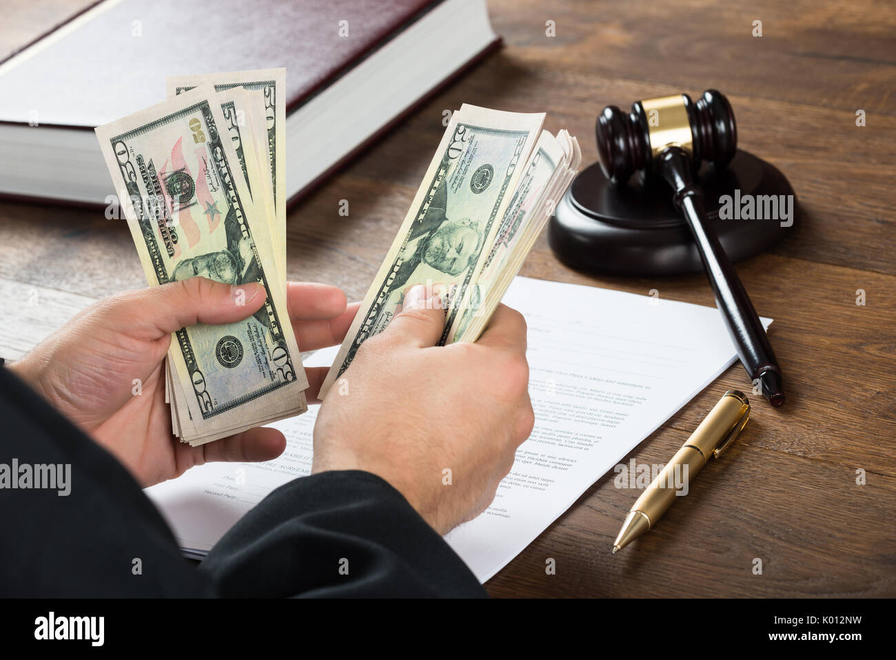 High angle view of corrupt judge counting money at desk in courtroom Stock Photo