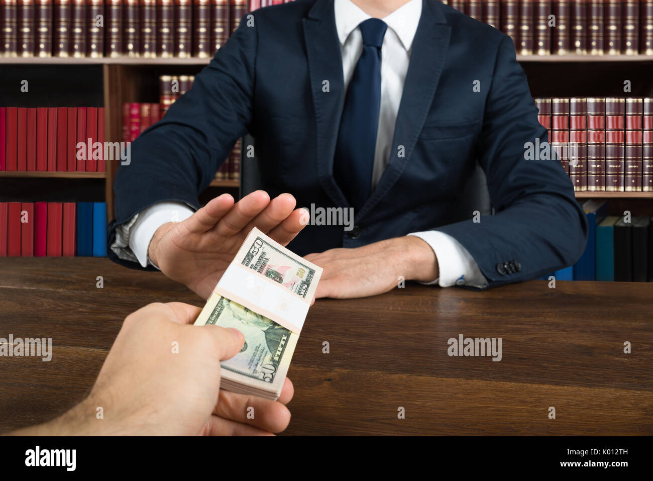 Midsection of lawyer refusing bribe to take from client at desk in courtroom Stock Photo