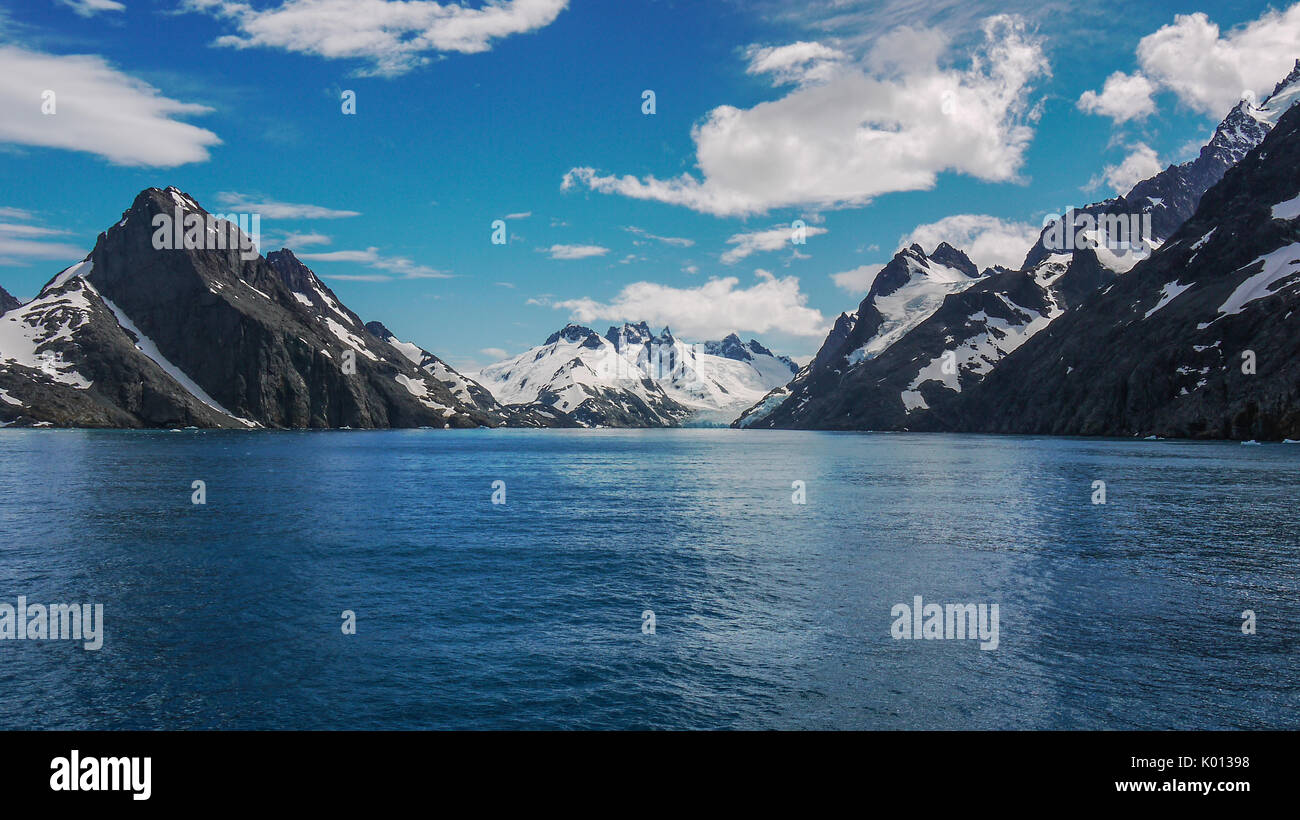 Dramatic scenery of glacial Drygalski Fjord on South Georgia Islands. Steep snow capped mountains beside deep bay. Stock Photo