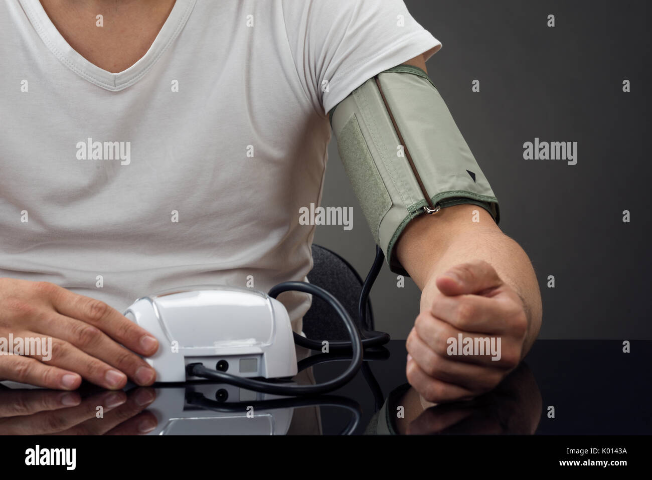 Midsection of man checking blood pressure at table against gray background - Stock Image