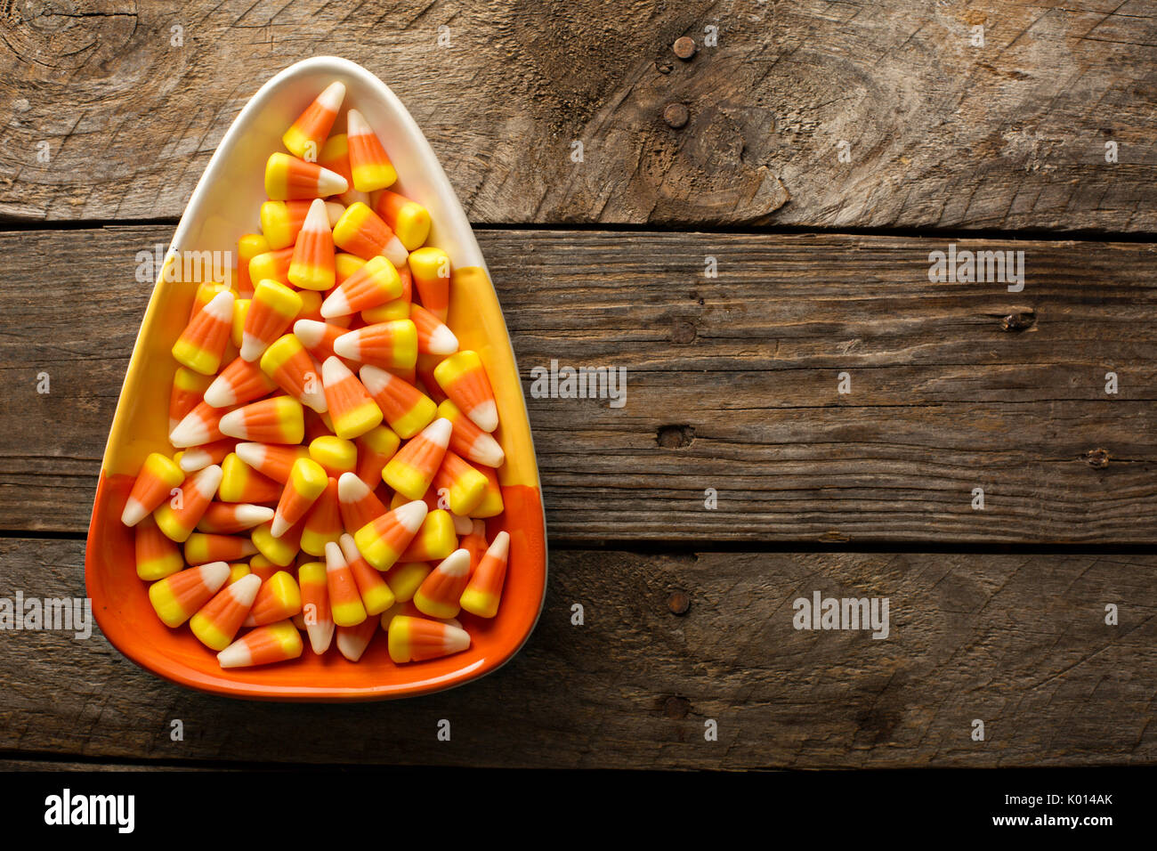 Candy corn in a bowl Halloween background - Stock Image