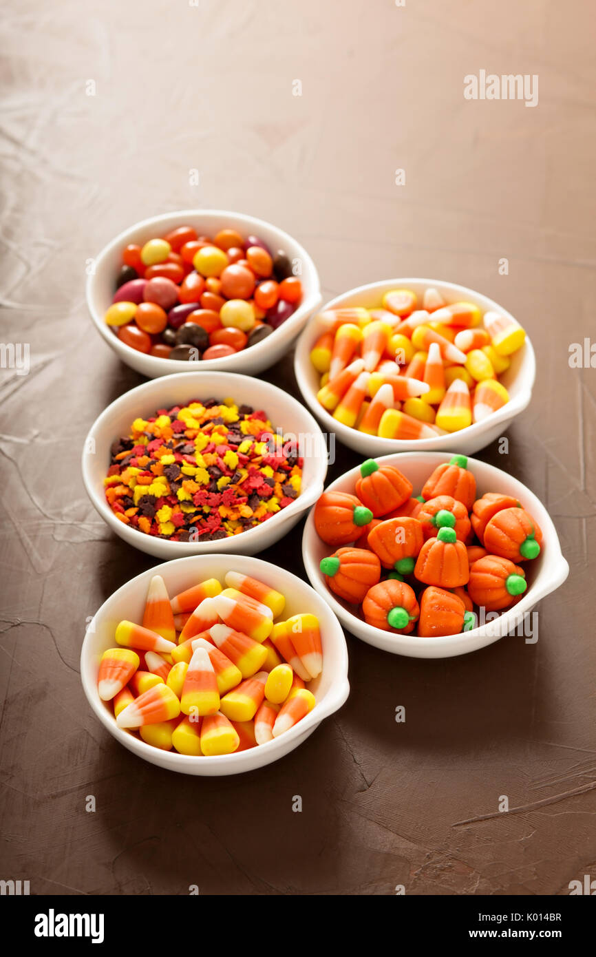 Halloween candy and sprinkles in white bowls - Stock Image