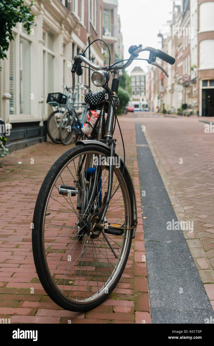 A bicycle parked on the footpath on a street in Amsterdam - Stock Image
