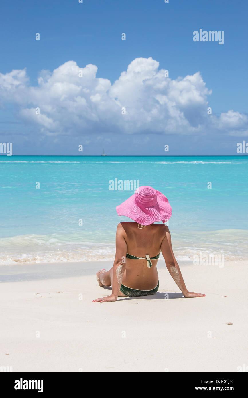 Tourist admires the turquoise Caribbean Sea Jolly Beach Antigua and Barbuda Leeward Island West Indies - Stock Image