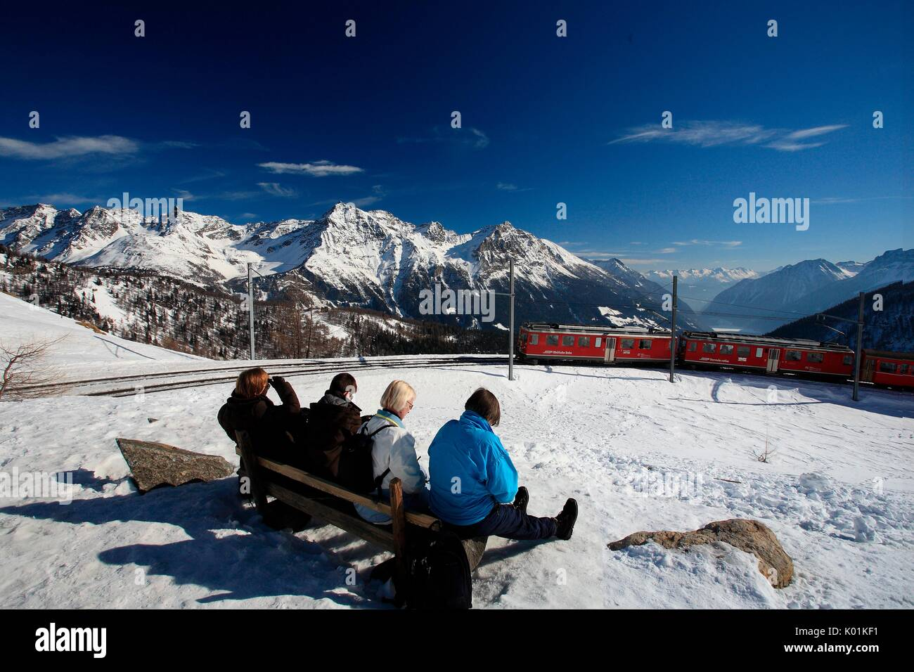 Tourists looking at the Bernina Express passing by the Alp Grum in the Val Poschiavo, Switzerland Europe - Stock Image