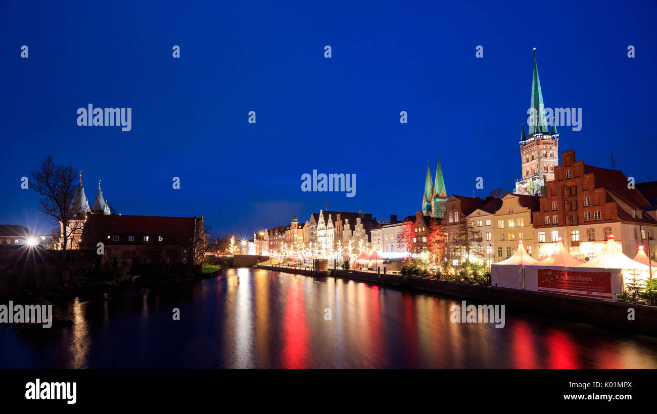 Night view of typical houses and the cathedral reflected in river Trave Lübeck Schleswig Holstein Germany Europe - Stock Image