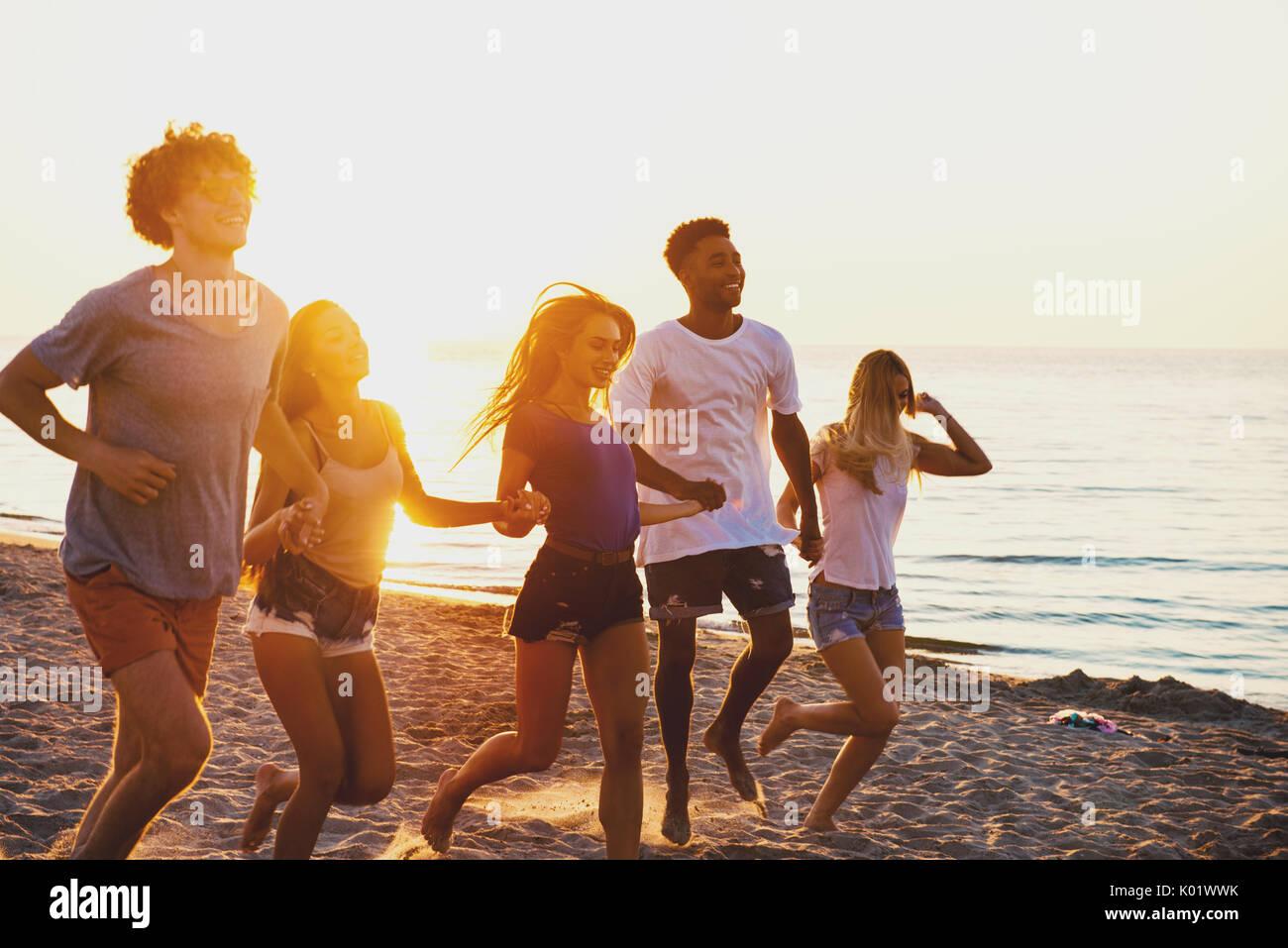 Group of happy friends having fun at ocean beach - Stock Image