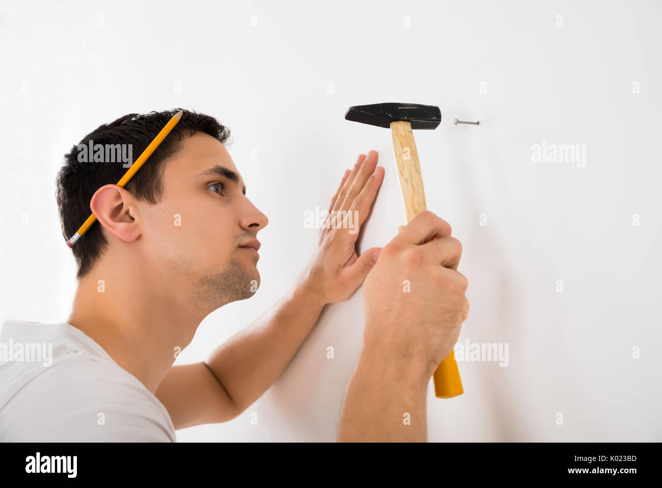 Side view of young man hammering nail on white wall at home - Stock Image