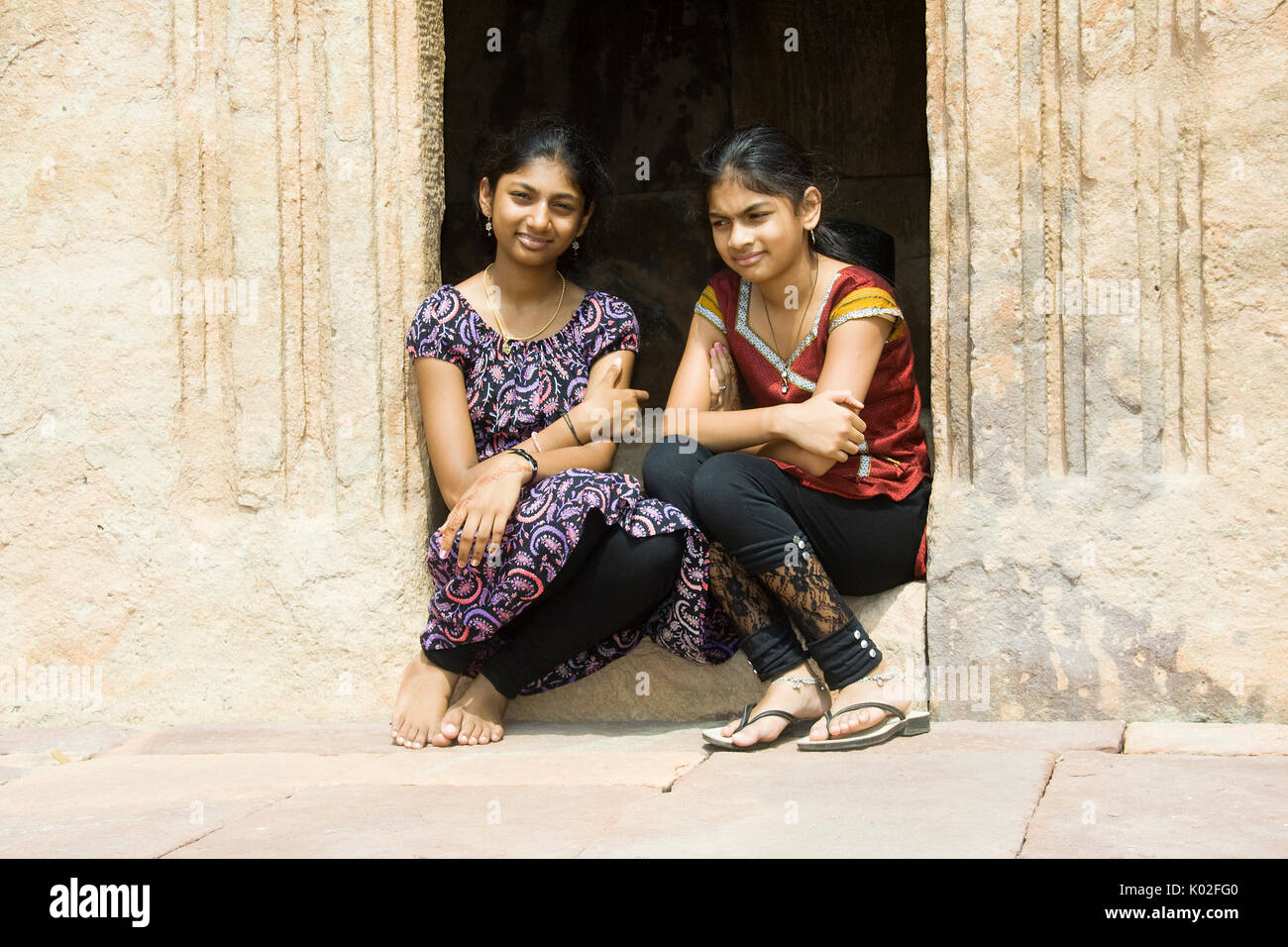 Two girls in happy disposition sitting on a doorstep Uploaded on 27jul17 Accepted - Stock Image