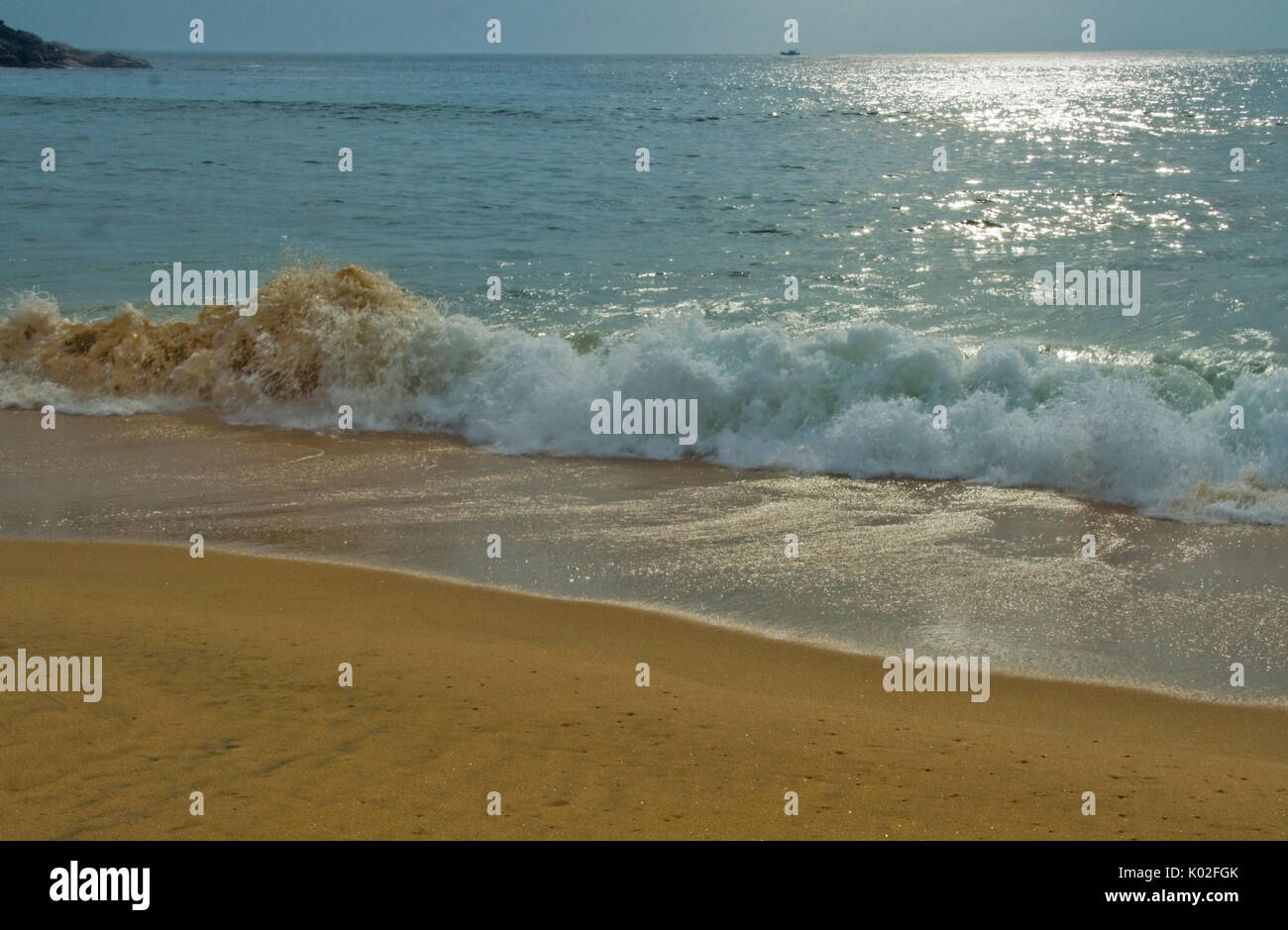 Breaking of foamy forceful wave on sandy shore of ocean Uploaded on 27jul17 Accepted - Stock Image