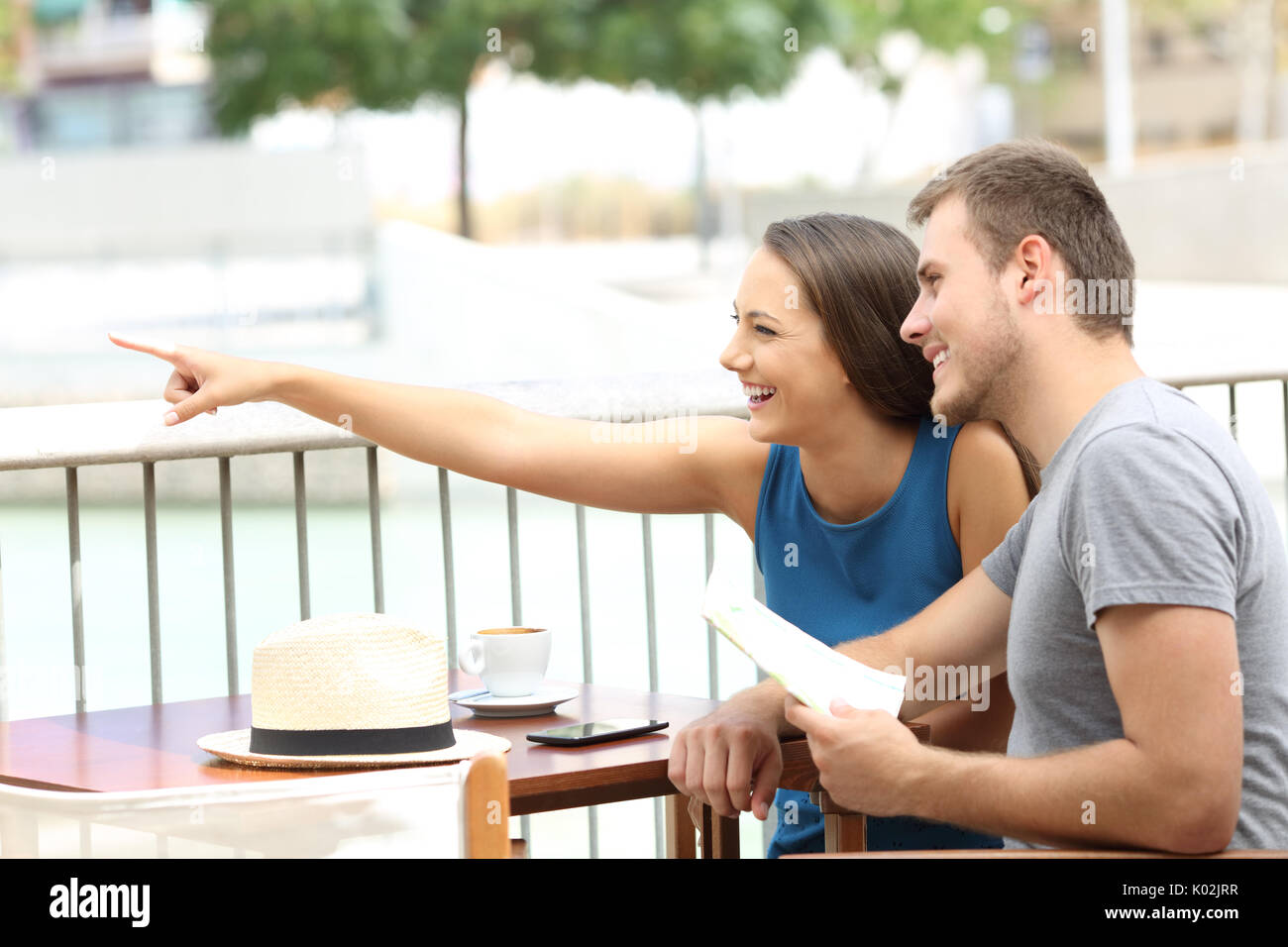 Couple ot tourists pointing locations sitting in a coffee shop - Stock Image