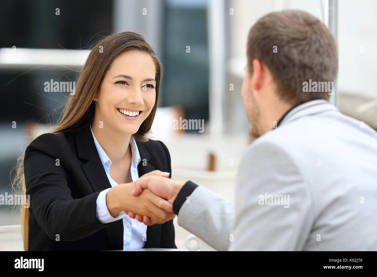 Two executives meeting and handshaking sitting in a coffee shop - Stock Image