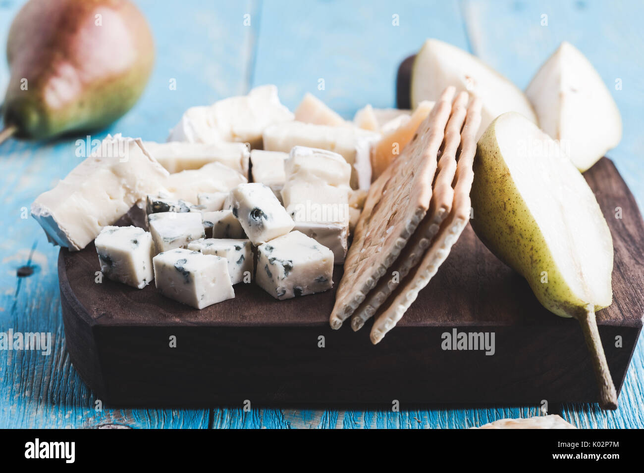 Cheese platter with blue cheese, soft cheese and aged cheese on rustic wooden board served with pear and crackers Stock Photo