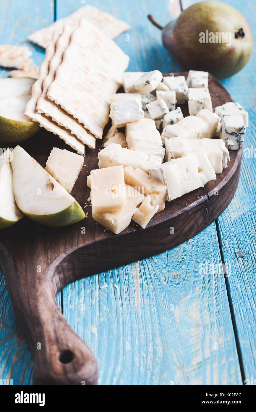 Cheese platter with blue cheese, soft cheese and aged cheese on rustic wooden board served with pear and crackers - Stock Image