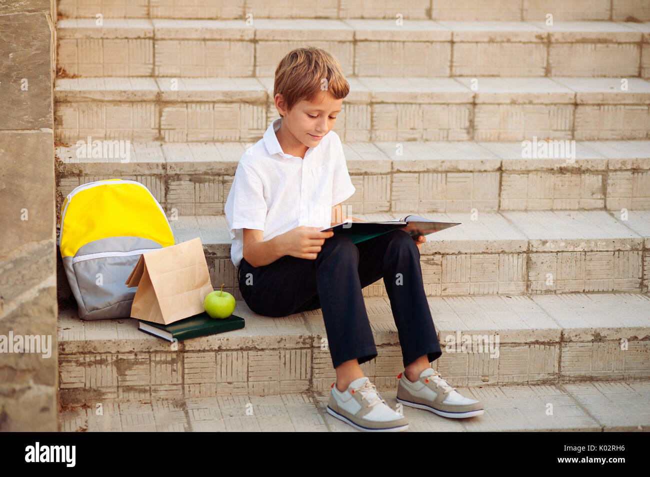 Small boy reading a book On the stairs of the school - Stock Image