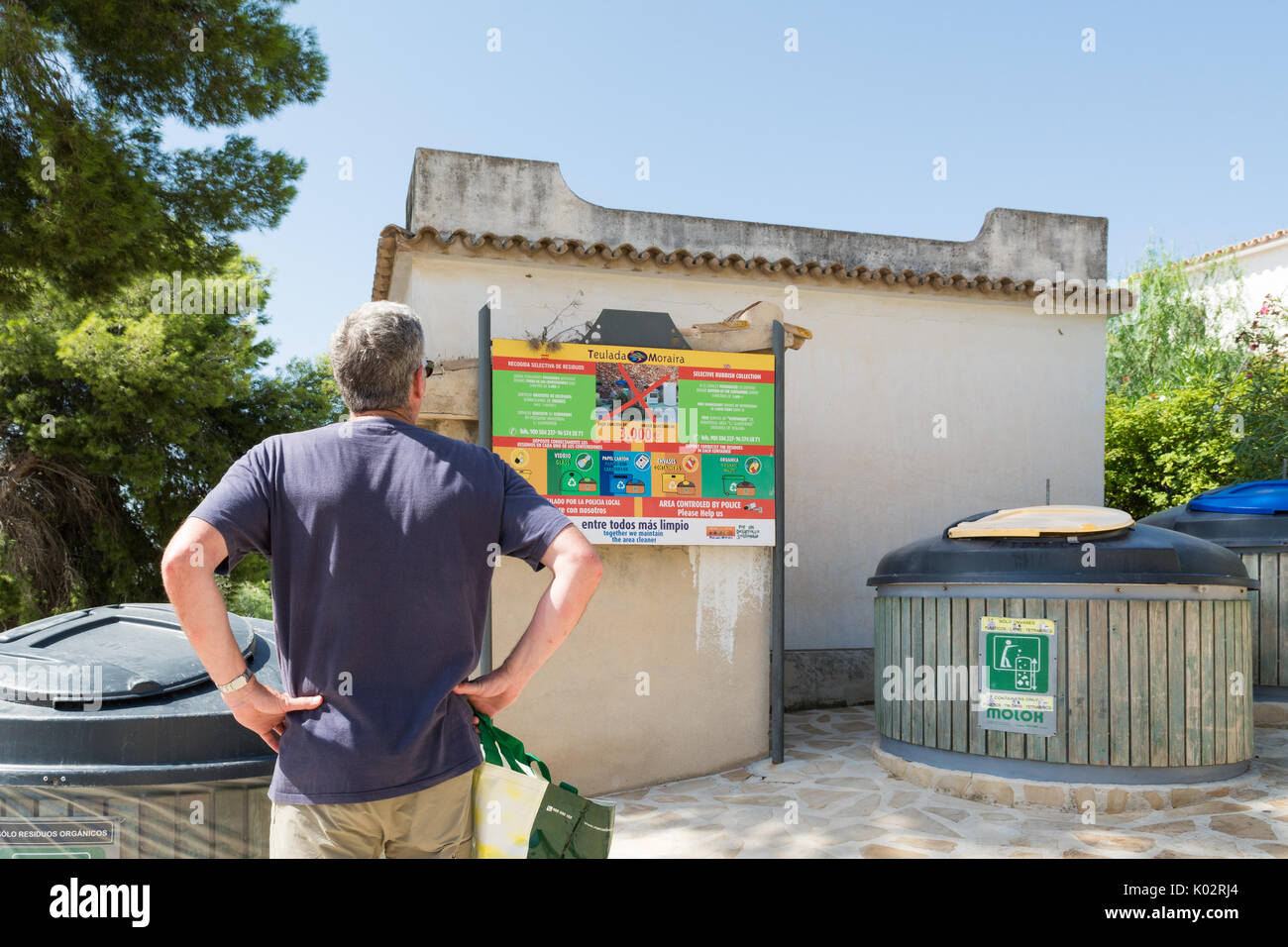 recycling on holiday - tourist looking at recycling facilities close to Spanish holiday villa - Stock Image