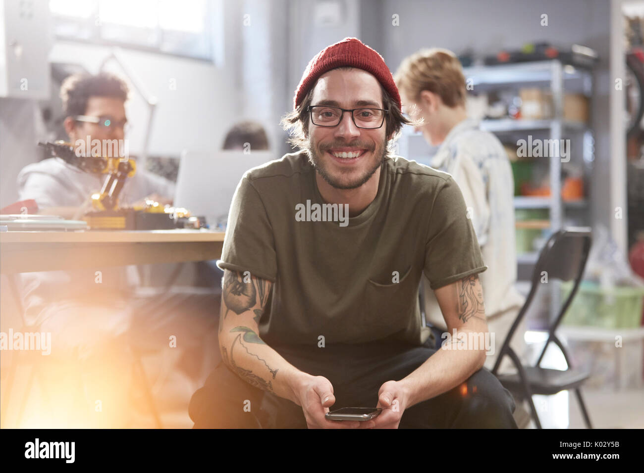 Portrait smiling confident male designer with cell phone - Stock Image
