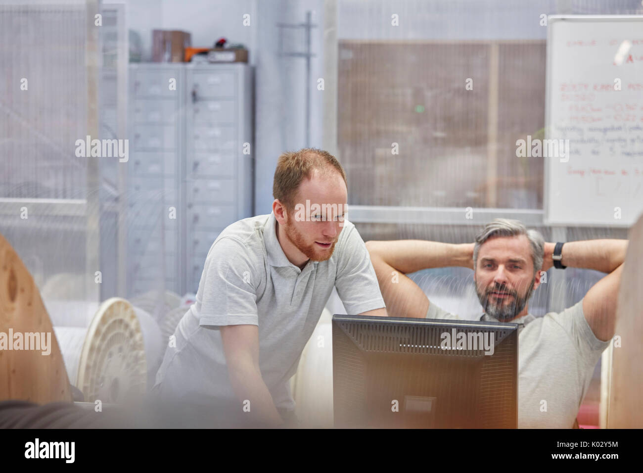 Male supervisors working at computer in factory - Stock Image