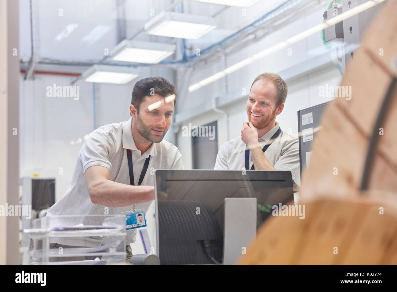 Male supervisors working at computer in factory office - Stock Image