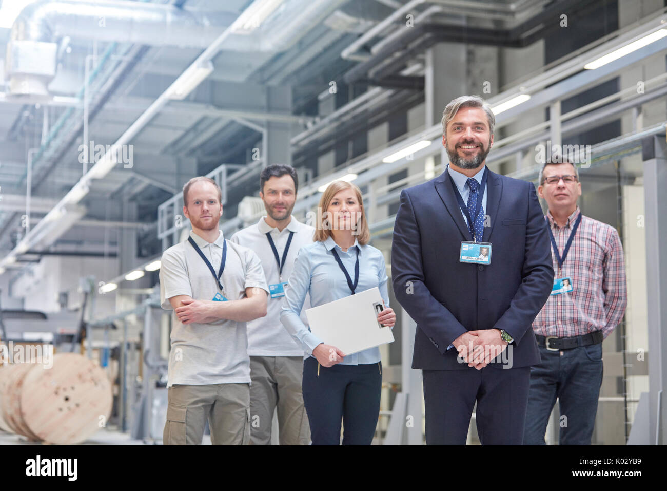 Portrait confident business owner and supervisors in fiber optics factory - Stock Image