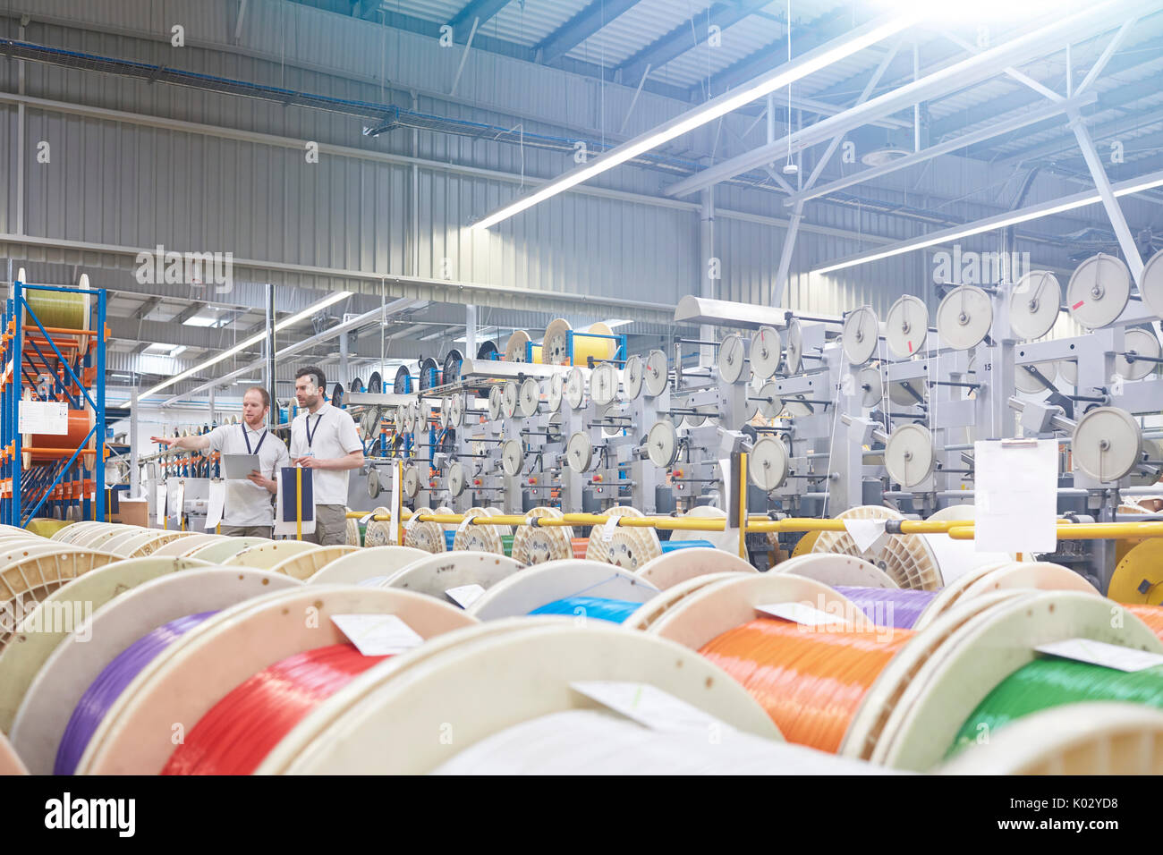 Male supervisor and worker checking inventory behind multicolor spools in fiber optics factory - Stock Image