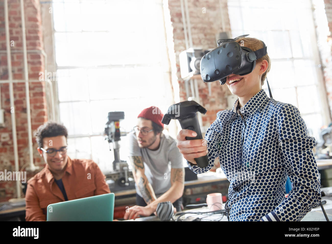 Female designer texting virtual reality simulator glasses and using joystick in workshop - Stock Image