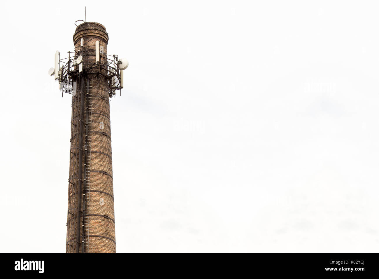 Old brick chimney with  antennas on cloudy sky background - Stock Image