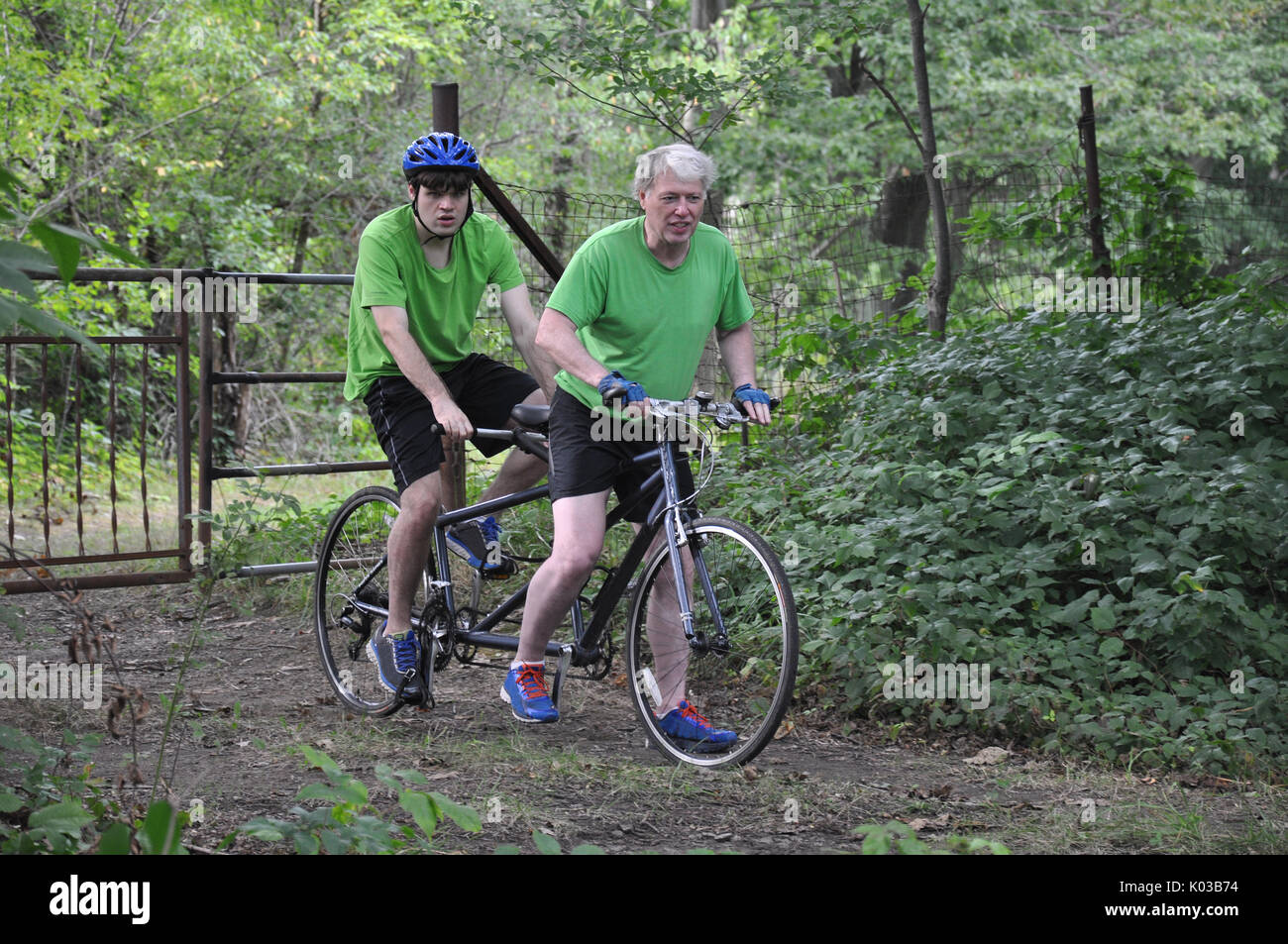 Father and Son on Tandem Mountain Hybrid Mountain Bike Cycling on the Western Reserve Greenway Trail in Ashtabula County, Ohio - Stock Image