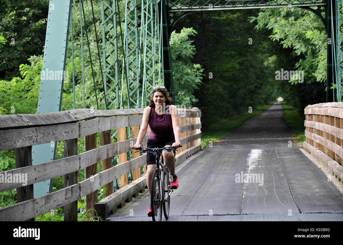Woman Bicycling over a Metal Bridge on the Western Reserve Greenway Trail in Ashtabula County, Ohio - Stock Image
